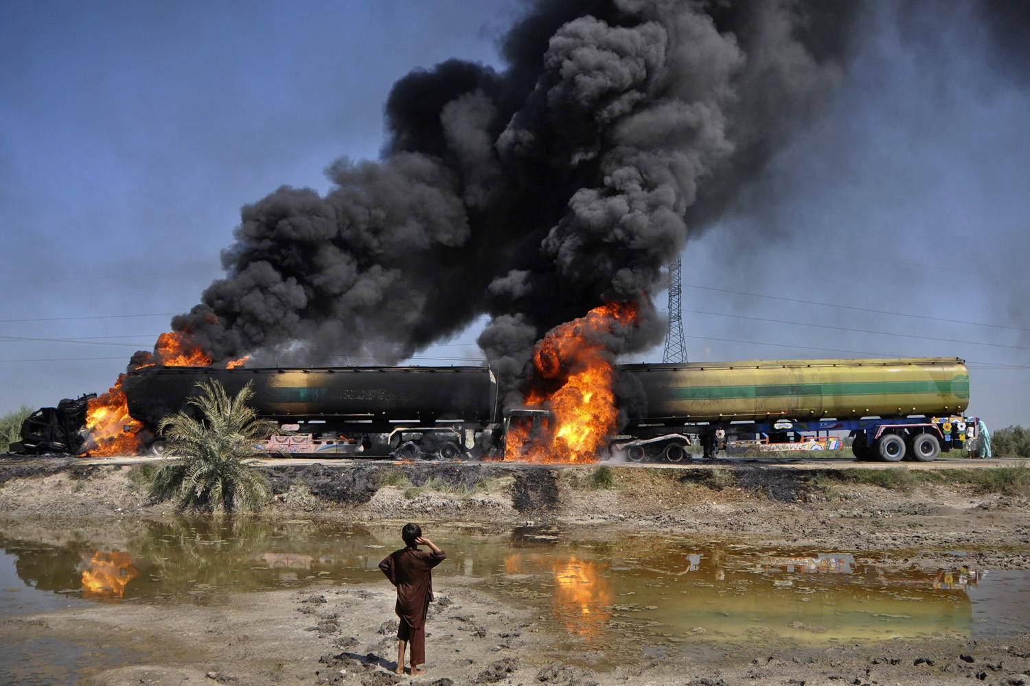 October 13, 2011. A boy looks at a plume of smoke rising from fuel trucks after they were attacked by unidentified gunmen on a highway near Shikarpur, about 39 km (24 miles) from Sukkur in Pakistan's Sindh province.