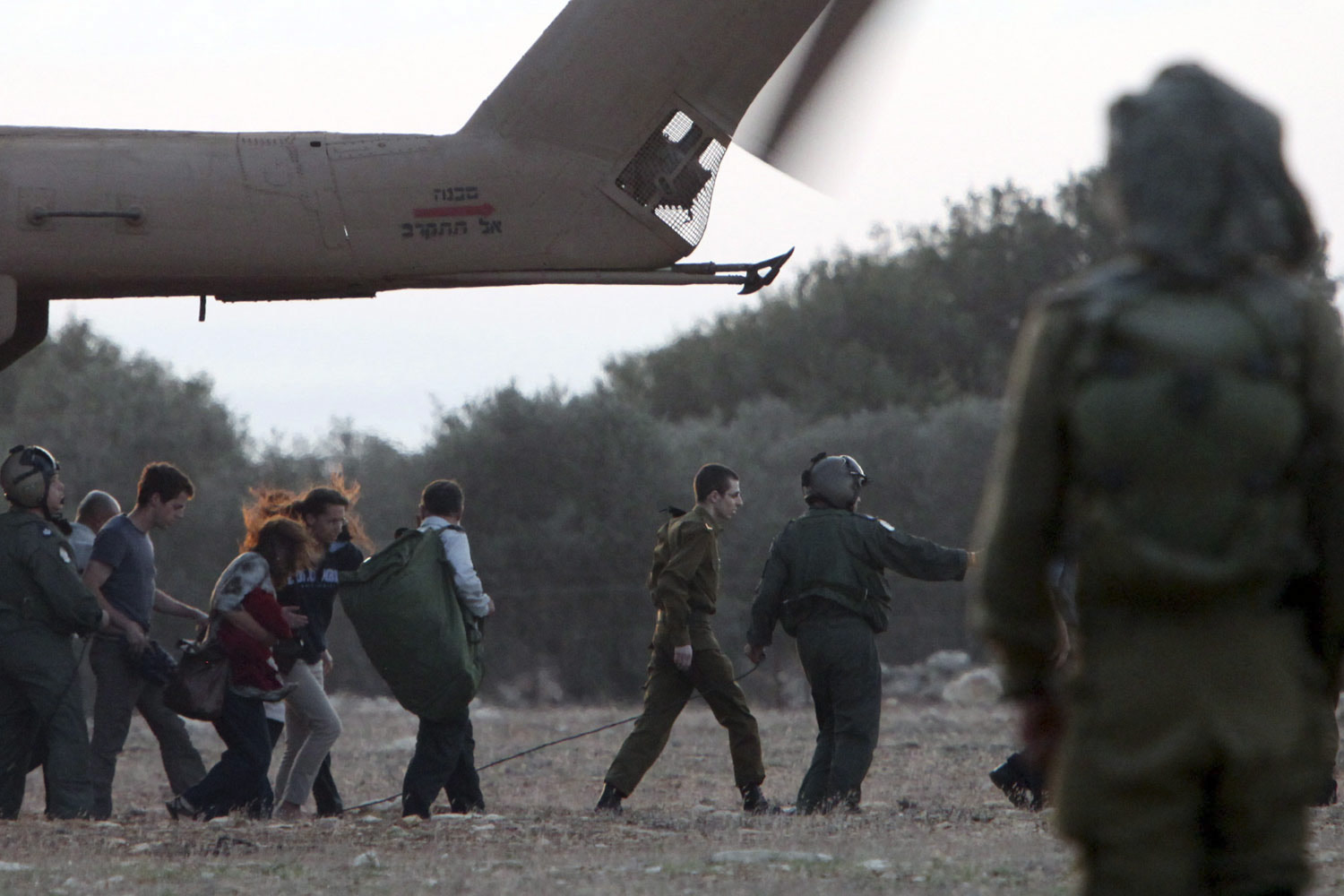 October 18, 2011. In the company of members of his family, Israeli solider Gilad Shalit is guided from an army helicopter. After being captured by Hamas militants in 2006 and spending five years in captivity in Gaza, Shalit was freed in exchange for the release of more than 1,000 Palestinians from Israeli jails.