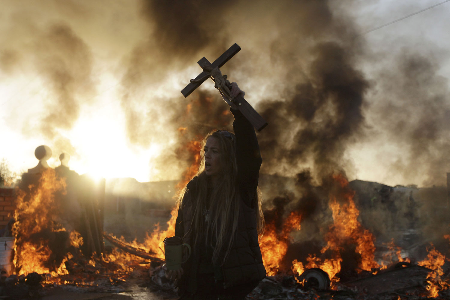 October 19, 2011. An Irish traveler resident holds up a cross for the media, in front of a burning barricade during evictions at the Dale Farm travelers site, near Basildon England, 30 miles east of London.