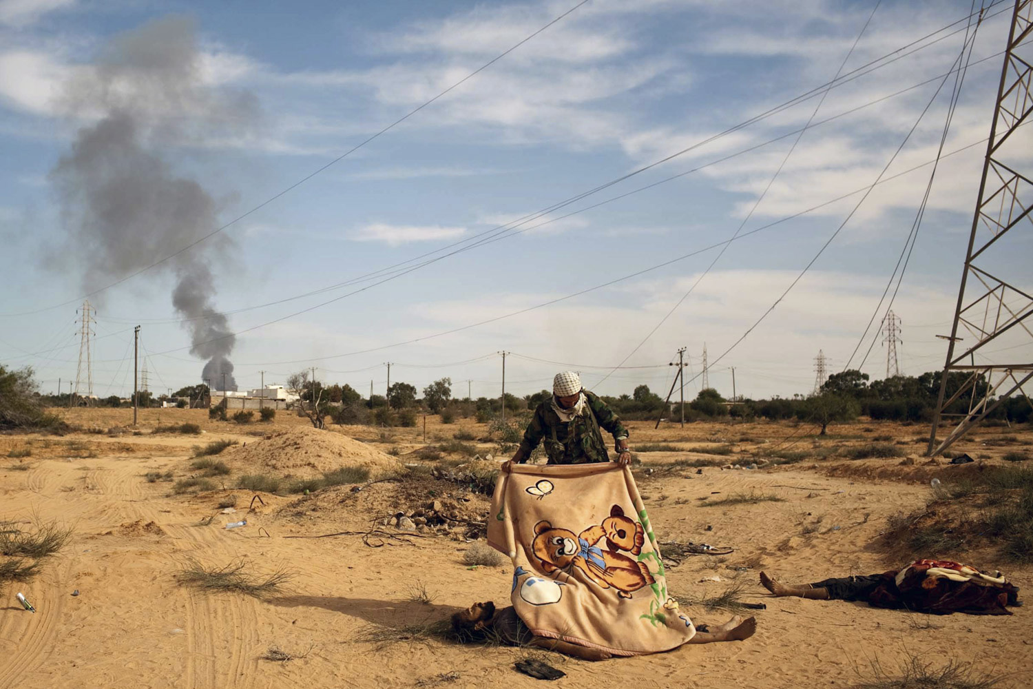 October 21, 2011. A Libyan rebel fighter covers a dead body of an alleged Muammar Gaddafi loyalist, killed by a NATO air strike in outskirts of Sirt, Libya.