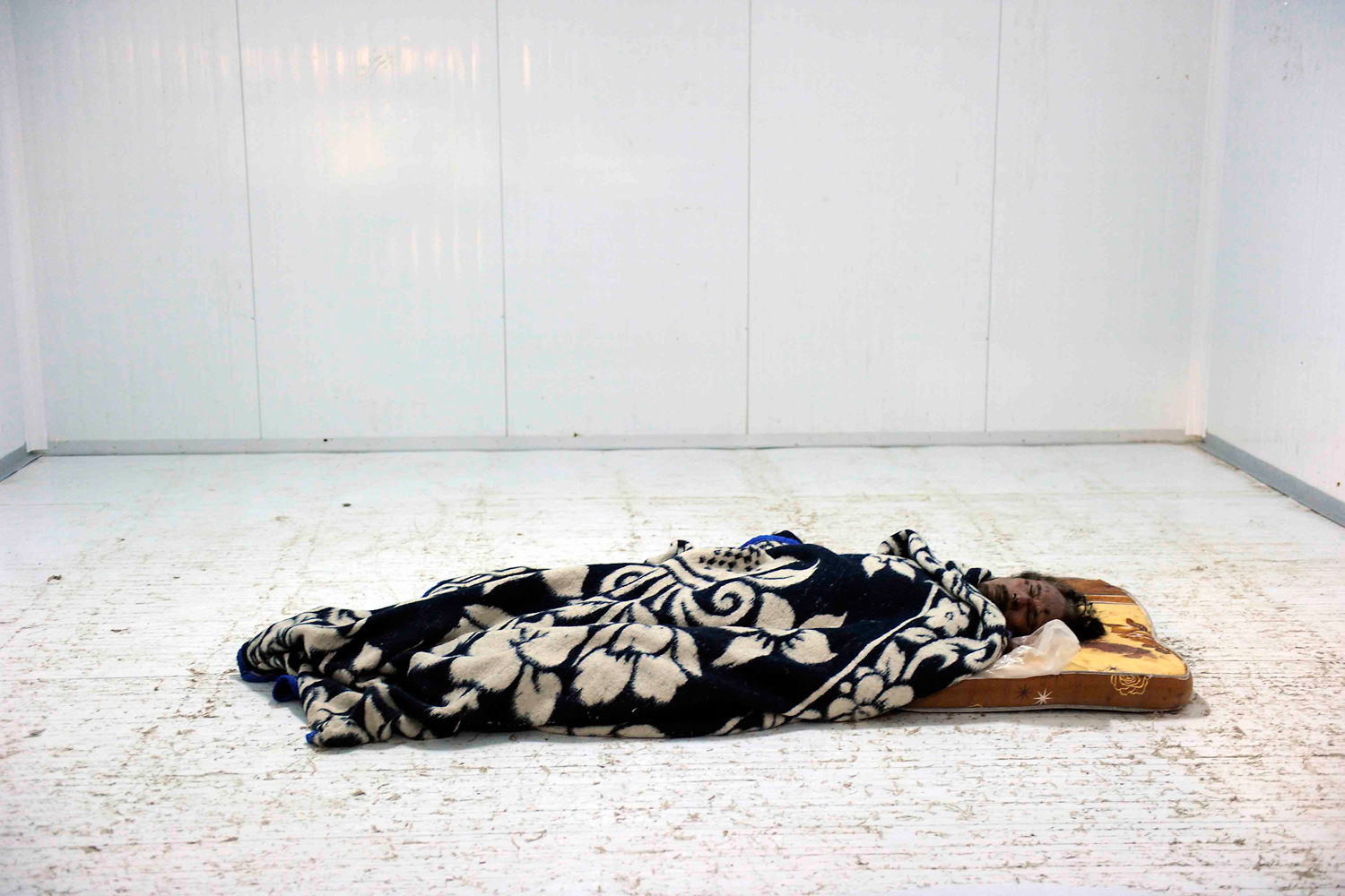 October 22, 2011. The body of former Libyan dictator Gaddafi lays in a refrigerated chamber usually used for storing vegetables in the Arab Market in Misrata.