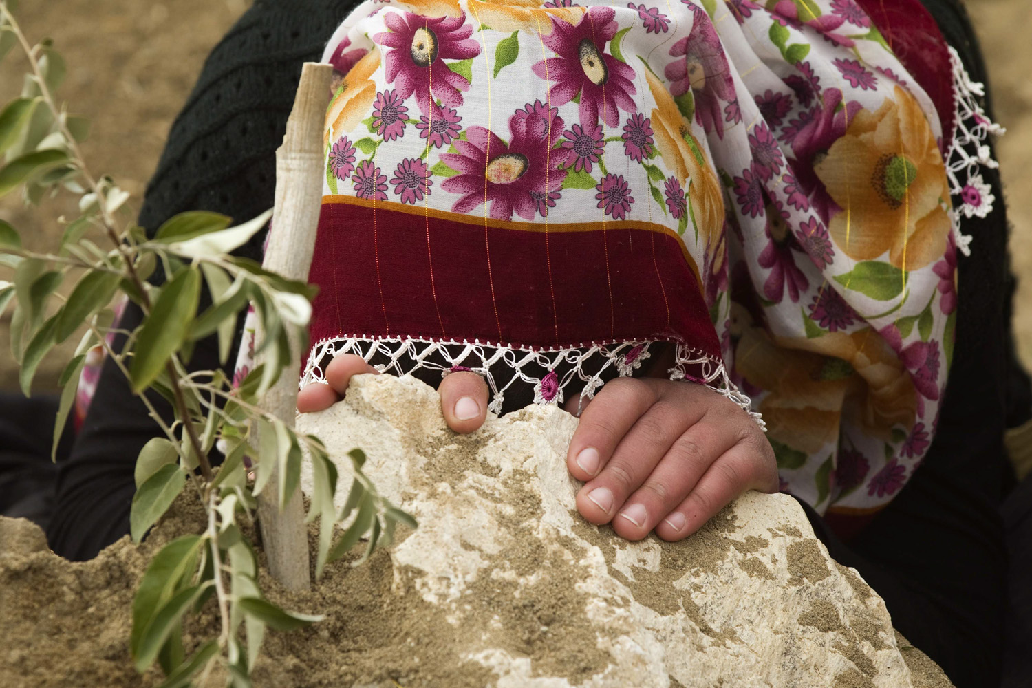 October 25, 2011. A woman mourns as she sits next to a grave of her relative, killed during an earthquake, in Ercis, Turkey.