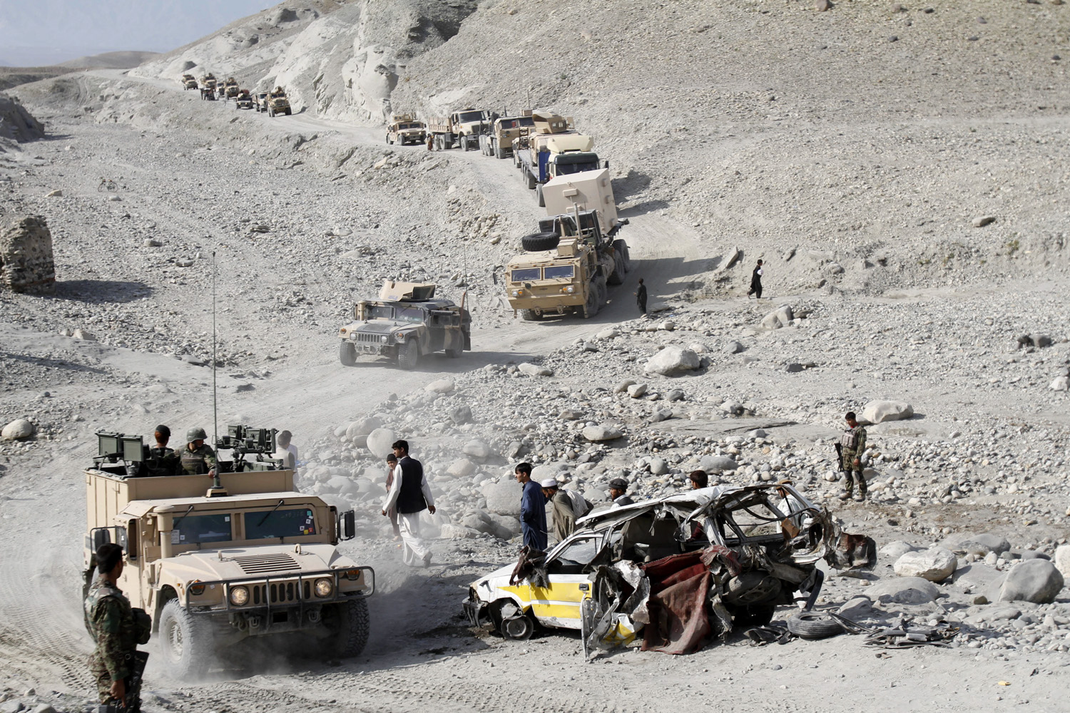 October 28, 2011. Afghan security men stand next to the wreckage of a civilian car which was hit by a roadside bomb as a U.S.-led coalition convoy moves by, in Nangarhar province, east of Kabul, Afghanistan.