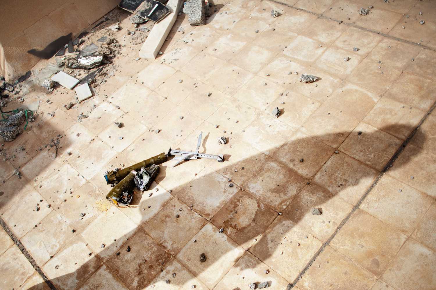 October 30, 2011. The shadow of a resident of the restive city of Bani Walid, Libya is caste near the wreck of a rocket propelled grenade on the roof of a damaged building.