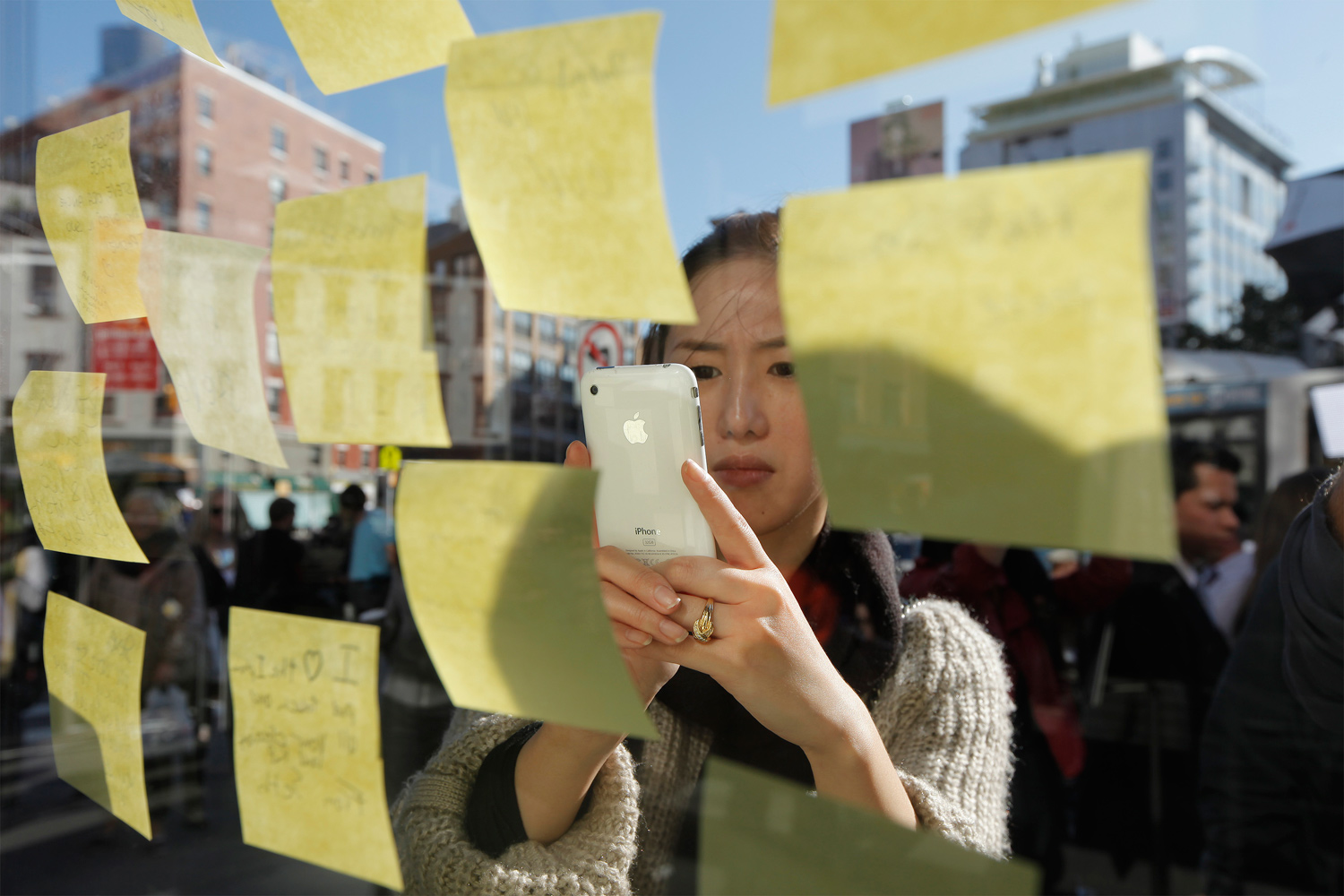 October 6, 2011. A woman uses her iPhone to photograph notes left memorializing Steve Jobs on the exterior of Apple's 14th Street store in New York. Apple Inc co-founder and former CEO Steve Jobs died on at the age of 56 after a years-long and highly public battle with cancer and other health issues.
