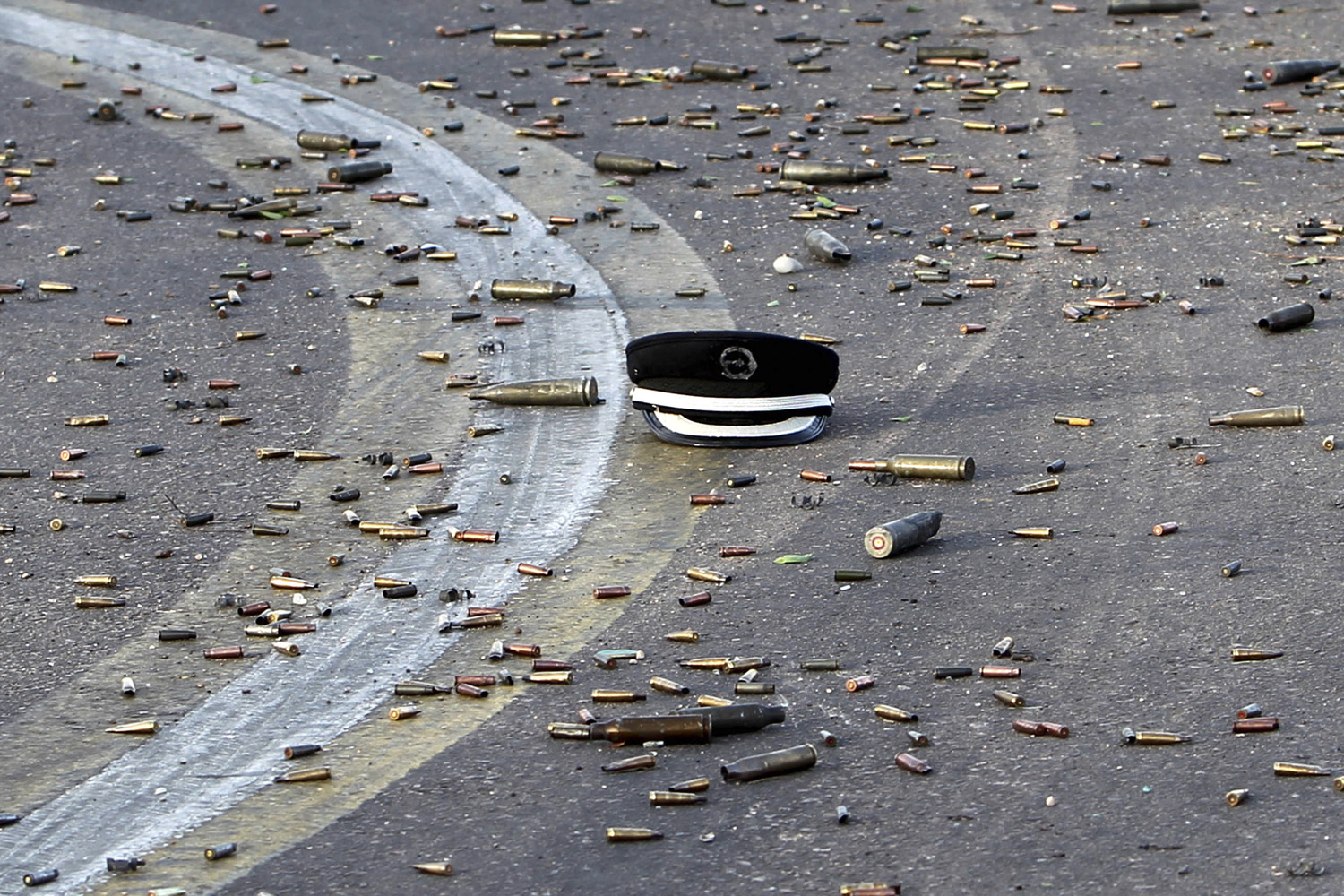October 9, 2011. A hat that belonged to a member of Gaddafi's forces is seen on the ground amid spent bullet cartridges during heavy clashes against anti-Gaddafi forces outside the State Security compound in Sirt.