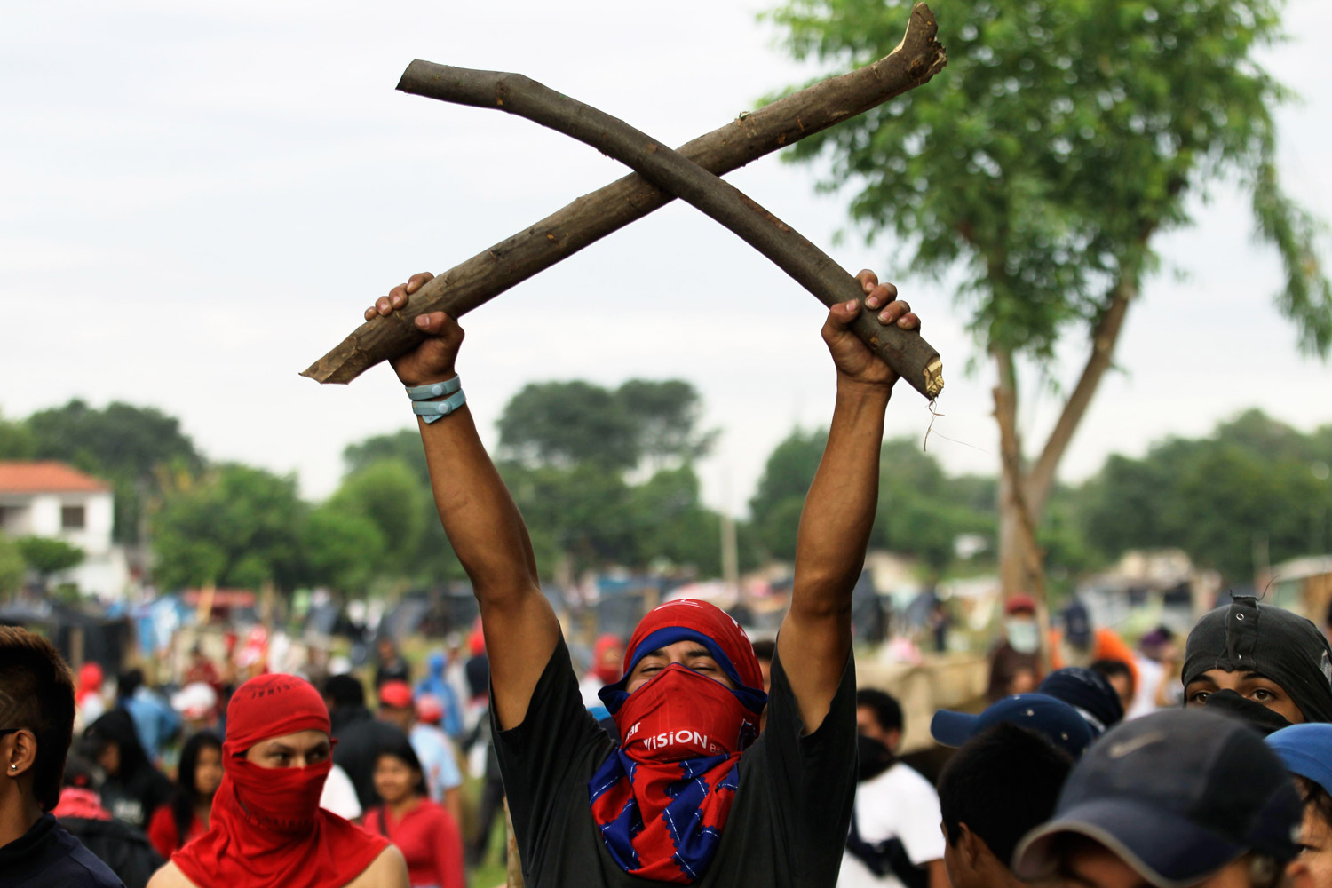 December 6, 2011. A man makes a warrior's gesture during a clash with riot police in the Paraguayan capital of Asunción. More than 400 families who illegally occupied an area belonging to the city government were evicted.