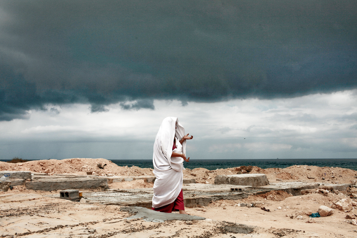 September 9, 2011. Under an ominous sky, Eyadea Elspaie visits the grave site of his son, Tareq Elspaie, who was killed by Gaddafi loyalists in August.