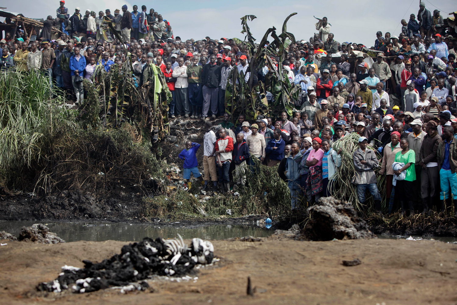 September 12, 2011. Residents of the area look on from across a small river at bodies of victims lying on the other side, after a pipeline explosion in Nairobi, Kenya.