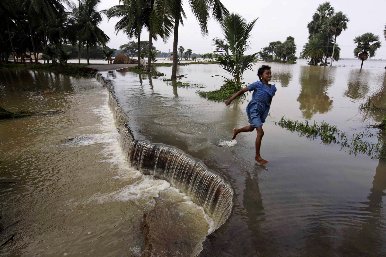 September 16, 2011. A girl runs across a flooded road as water recedes in Puri district, about 55 kilometers (34 miles) from the eastern Indian city of Bhubaneshwar.