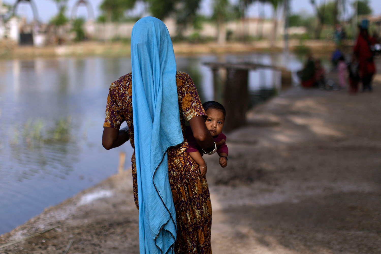 September 22, 2011. A displaced Pakistani child looks on while being held by her mother as they and others take refuge in a college in Tando Muhammad Khan near Hyderabad, Pakistan, after fleeing their flood-hit homes.