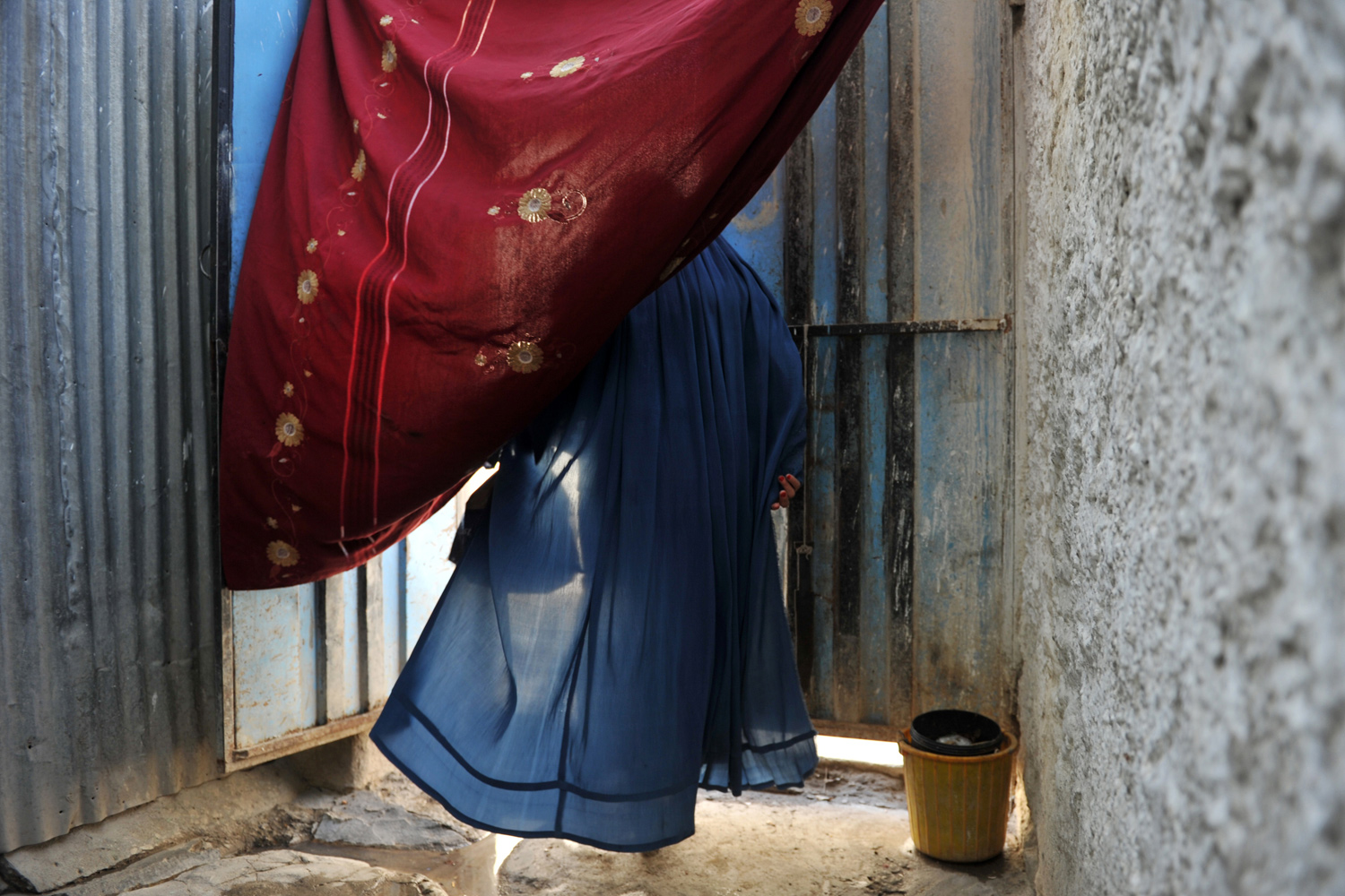 September 28, 2011. An Afghan burqa-clad woman leaves her home in Kabul. Ten years after the Taliban was toppled, most of Afghan women continue wearing burqas.