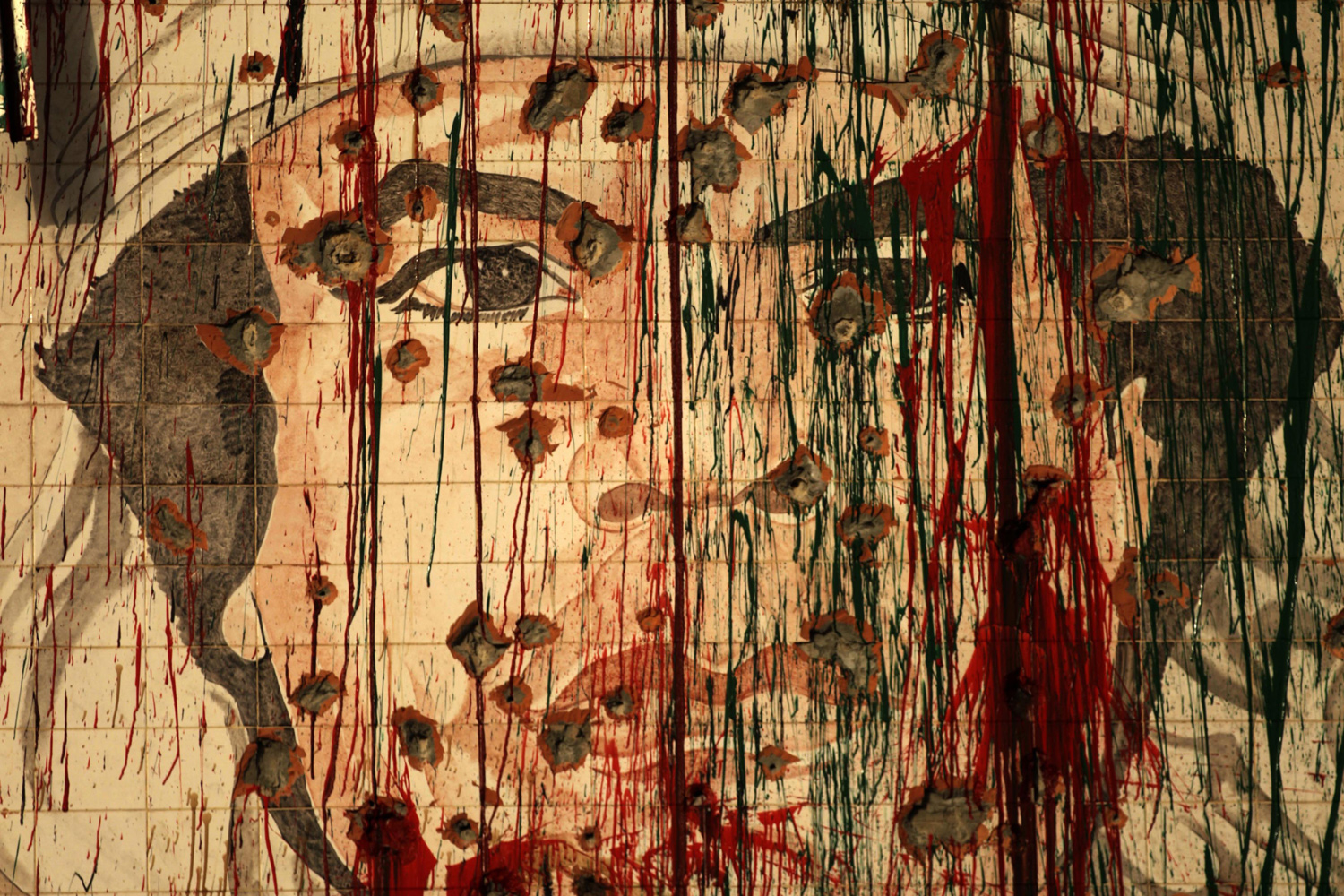 September 1, 2011. A defaced portrait of Libyan leader Muammar Gaddafi is pictured in Tripoli as the fallen strongman vowed again not to surrender, in a message broadcast on the 42nd anniversary of the coup which brought him to power.