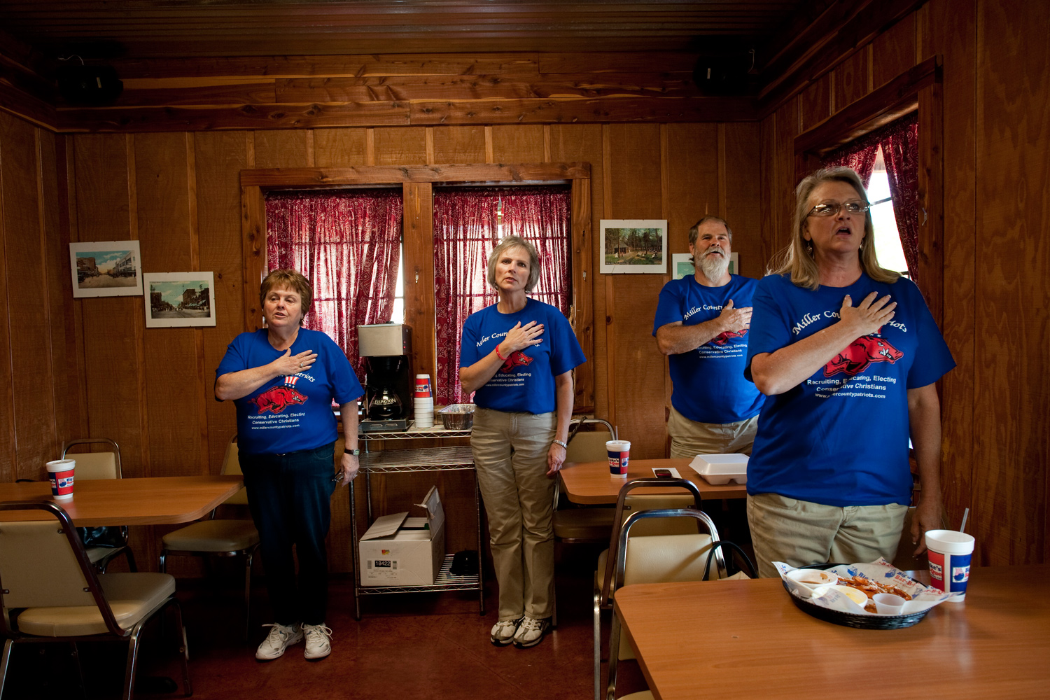 September 20, 2011. From left to right: Sue O'neal, 65, Texarkana, Mary Anne Green, 54, Wayne green, 59, all members of The Patriot Party, an offshoot of the Tea Party, bow their heads in prayer before a meeting at Big Jakes BBQ in Texarkana, Arkansas.
