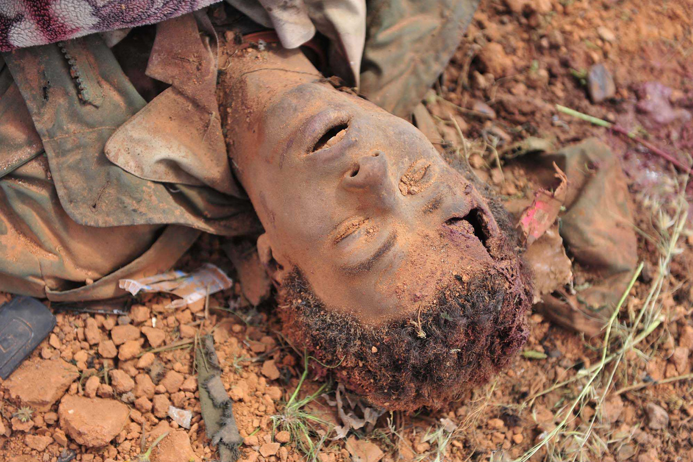 March 20, 2011. The body of a Muammar Gaddafi loyalist lies on the ground as smoke billows from damaged tanks belonging to Gaddafi forces in al-Wayfiyah, Libya.