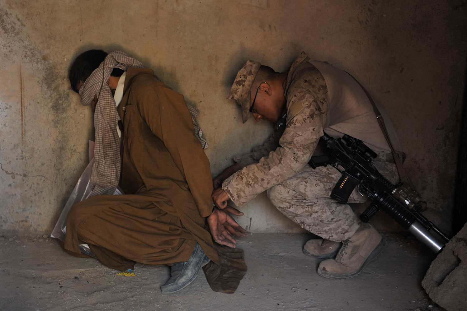 May 23, 2011. A U.S. Marine from 3rd Battalion 9th Marines Kodiak Company checks handcuffs of a detainee arrested after an early morning operation in Helmand Province, Afghanistan.