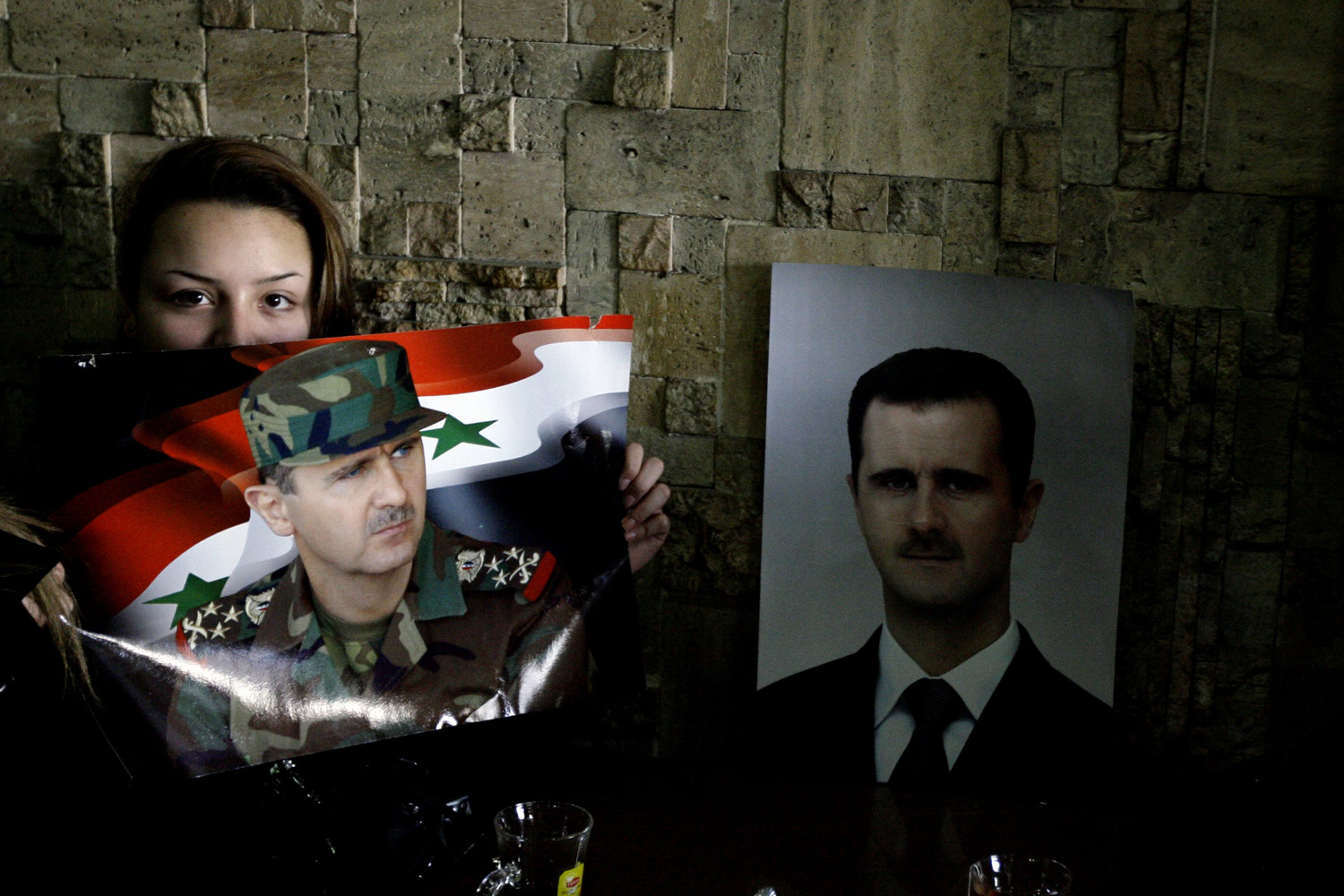 January 10, 2012. A Syrian woman holds up a picture of Syrian President Bashar al-Assad as she follows his speech on television at a cafe in Damascus.