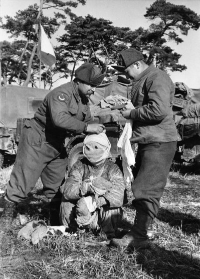 Turkish soldiers attend to a wounded prisoner, Korea, 1951.