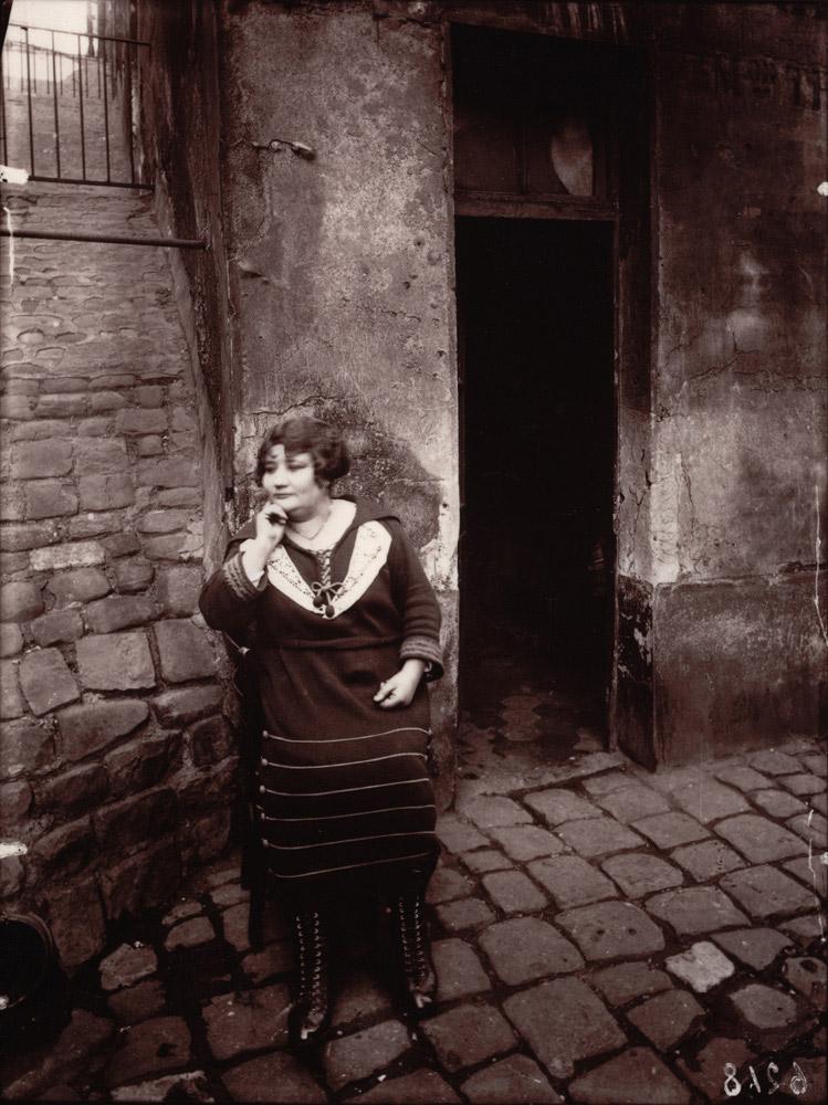 La Villette, rue Asselin, prostitute offering her services before her door, nineteenth arrondissement, March 1921
