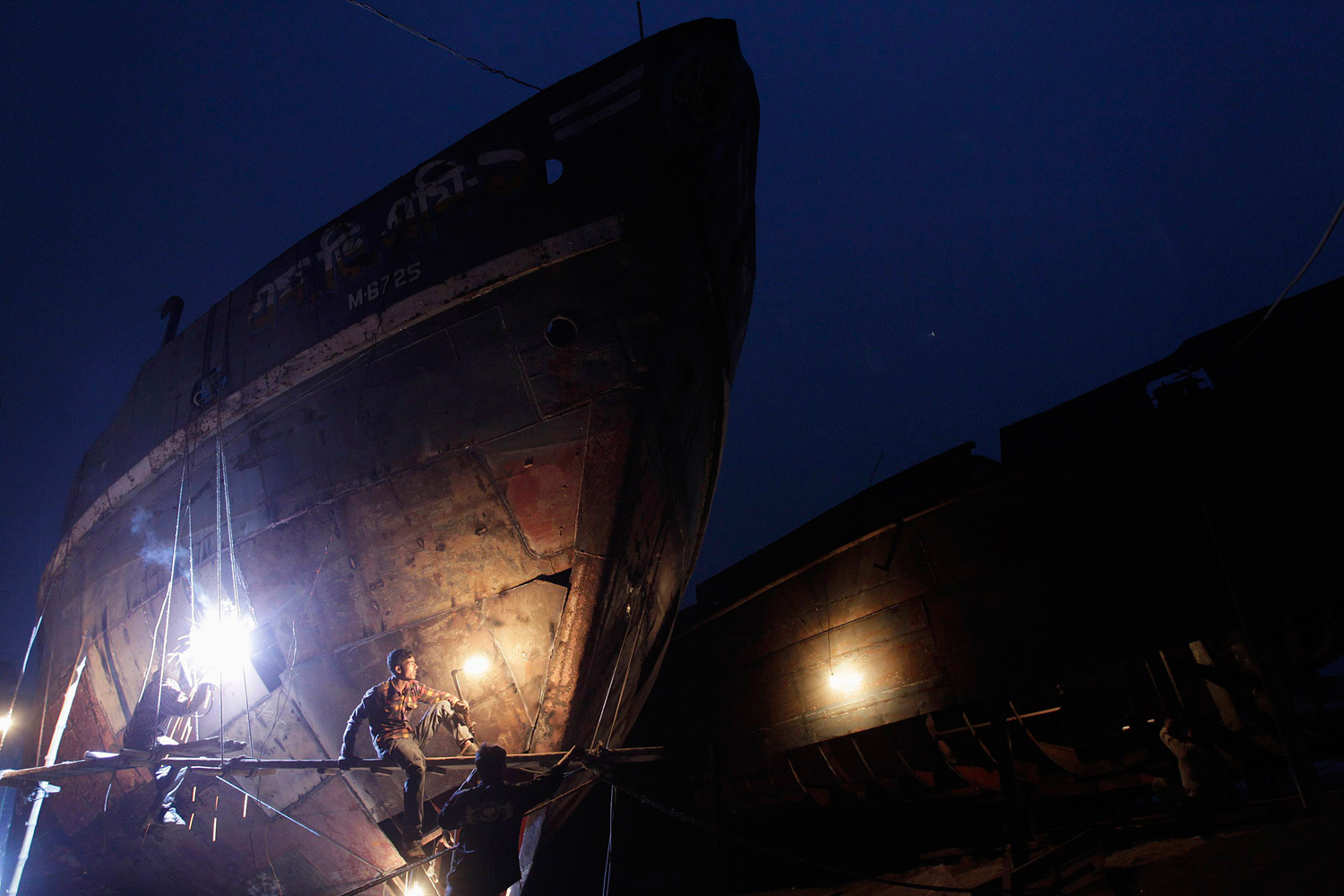 January 8, 2012. Workers weld at a ship-building yard next to Buriganga River in Dhaka.