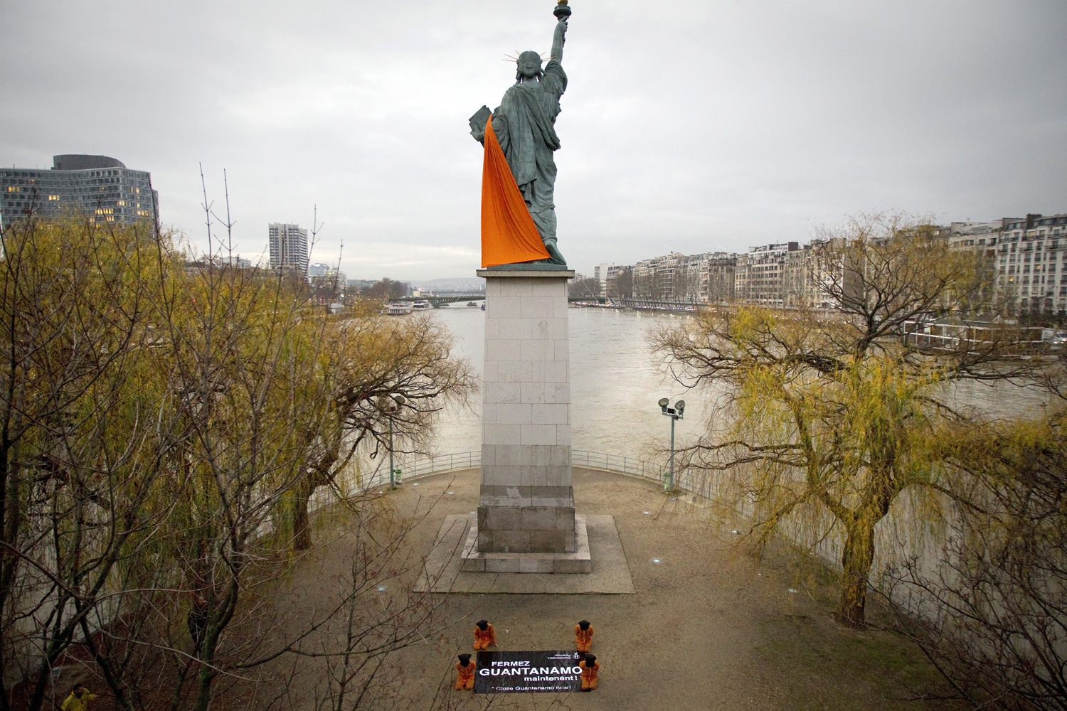January 10, 2012. Amnesty International activists, dressed in orange jumpsuits similar to those worn by prisoners at the US detention camp in Guantanamo Bay, demonstrate next to the scale model of the statue of Liberty in Paris against the 10th anniversary of the opening of the prison.