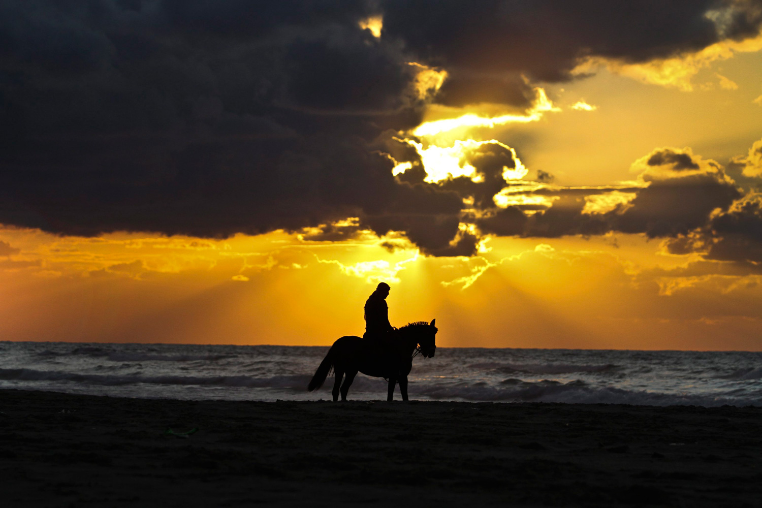 January 20, 2012. A Palestinian man is silhouetted against the setting sun as he rides a horses on a beach near Gaza City on a cold winter evening.