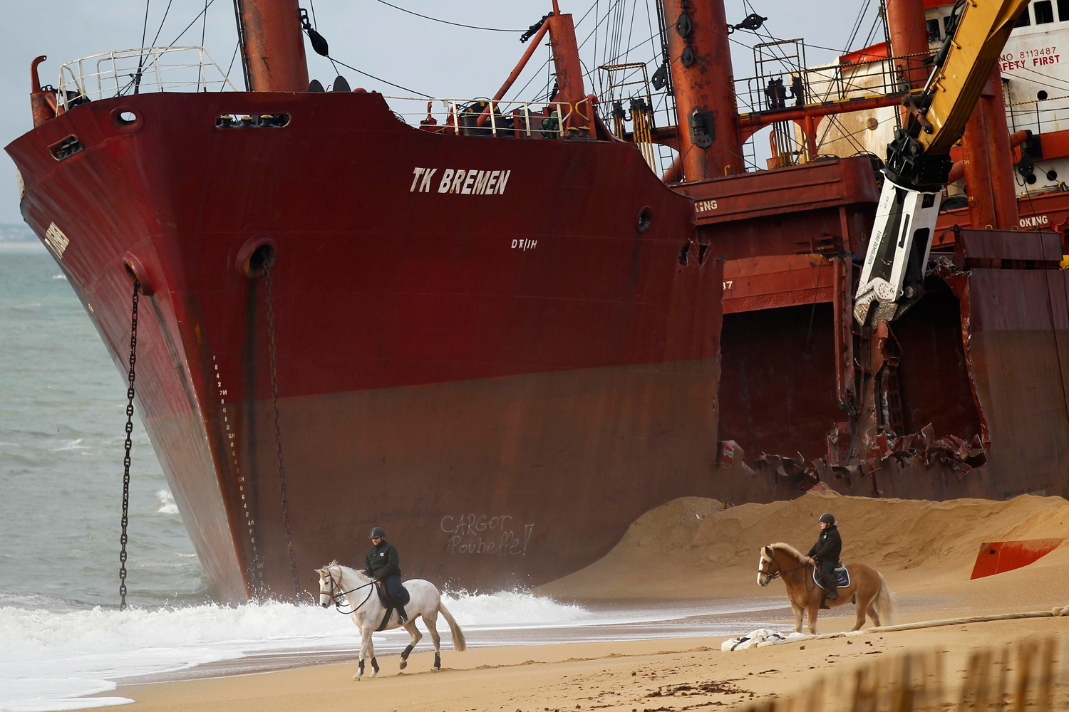 January 7, 2012. Security officers look on from their horses as a crane dismantles the Maltese-registered cargo ship in western France.