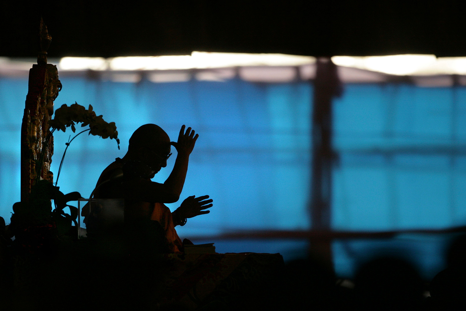 January 4, 2012. Tibetan spiritual leader the Dalai Lama is silhouetted as he teaches an assembly of monks and devotees during the Kalachakra Buddhist festival in Bodh Gaya, Bihar, India. Bodh Gaya is believed to be the place where Buddha attained enlightenment.
