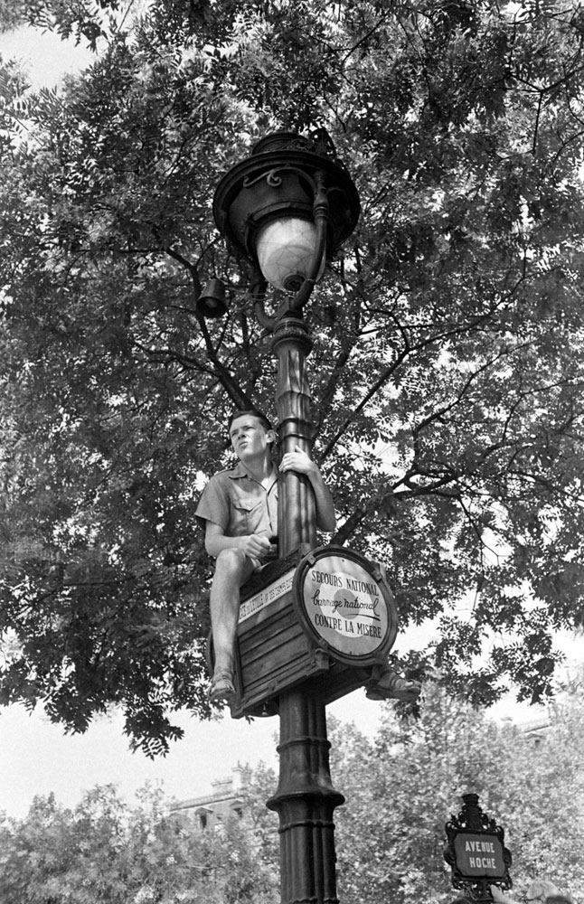 <strong>Not published in LIFE.</strong> A young man watches liberation celebrations from atop a light pole, Paris, August 1944.