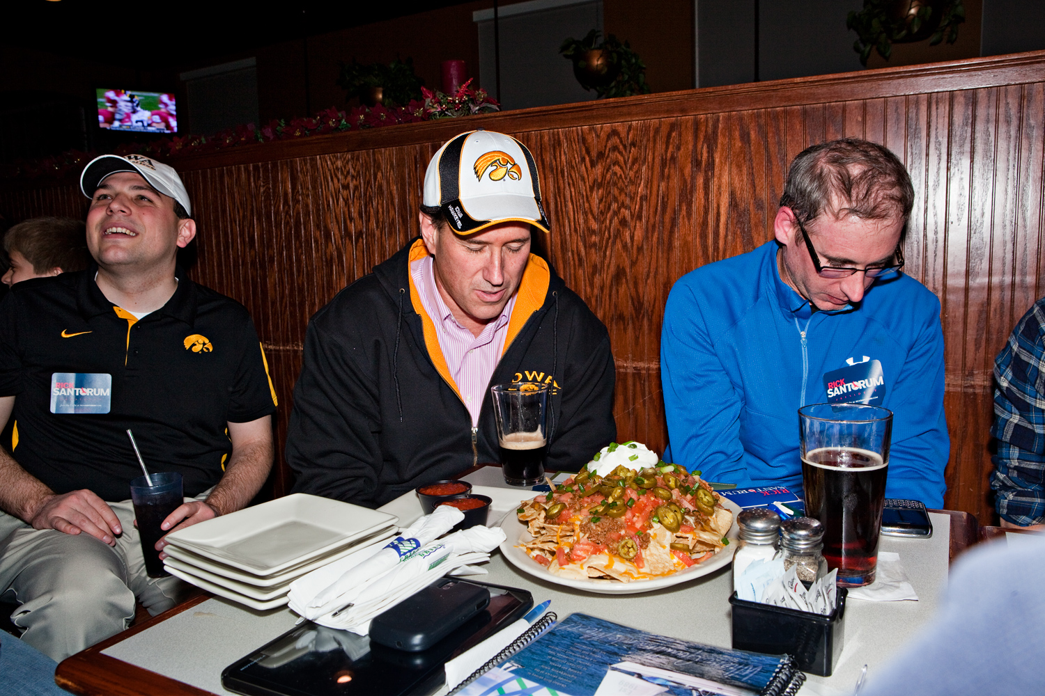 Rick Santorum prays before a meal of nachos at the Okoboji Grill while he campaigns in Johnston, Iowa on December 30, 2011.