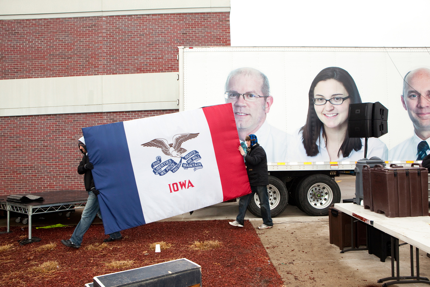 Mitt Romney supporters break down the set after a campaign event in Des Moines, Iowa on December 30, 2011.
