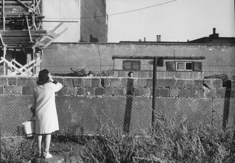 A mother and her daughter talk over the Berlin Wall.
