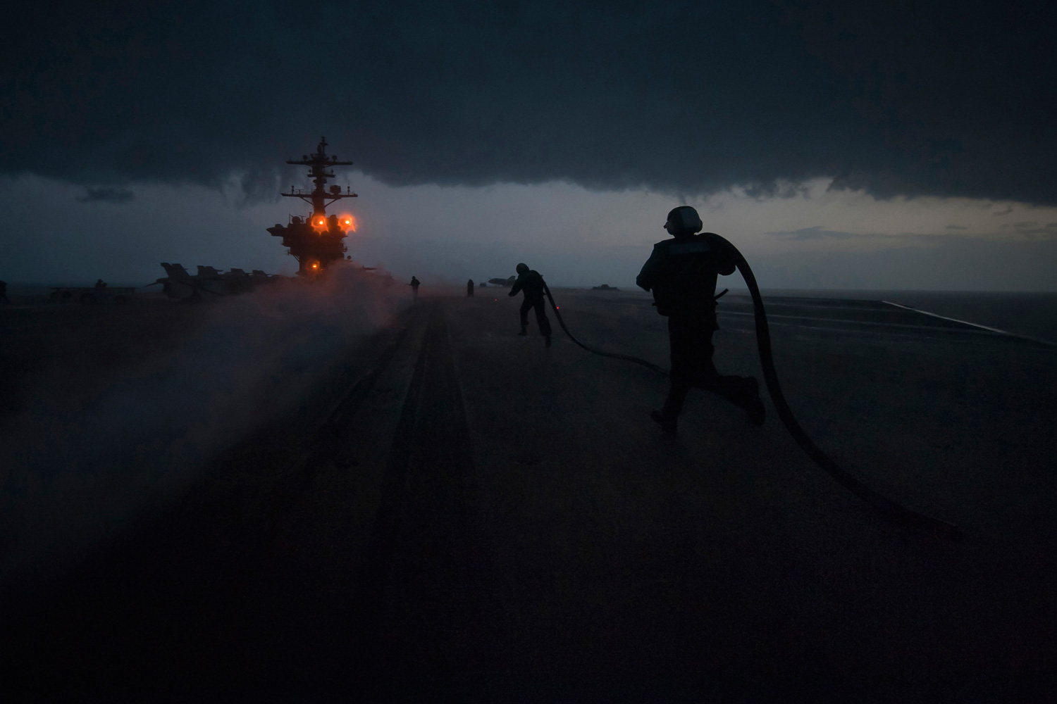 January 21, 2012. Sailors install slot seals in a catapult track after a launch as the aircraft carrier USS Carl Vinson passes through a storm in the Arabian Sea.