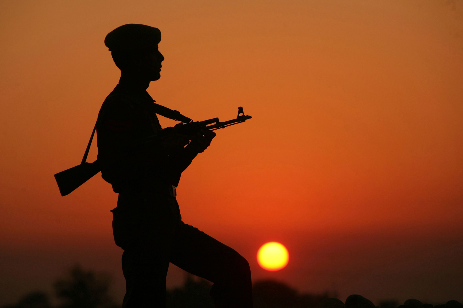 January 23, 2012. An Indian policeman is silhouetted against the setting sun as he stands guard on the banks of river Tawi before India's Republic Day celebrations in Jammu.