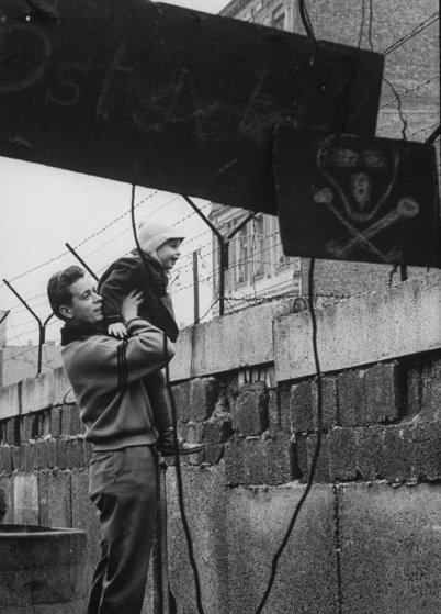 A West German man boosts up his son to give him a view of the other side of the Berlin Wall.