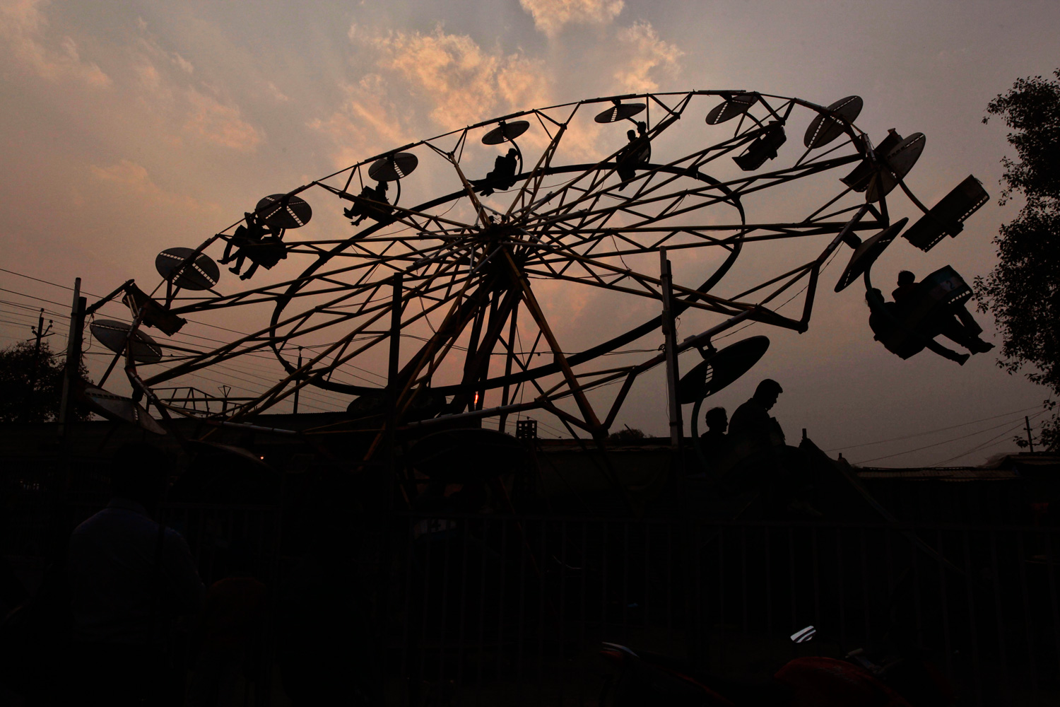 January 18, 2012. Hindu devotees are silhouetted as they ride a giant fair-ride wheel at the Sangam, the confluence of the rivers Ganges, Yamuna and the mythical Saraswati during the annual month-long Hindu religious fair of Magh Mela in Allahabad, India.