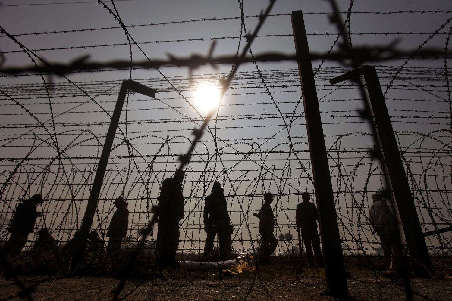 January 18, 2012. Indian Border Security Force soldiers are silhouetted as they stand guard at the site of an alleged shoot-out on the India-Pakistan border.