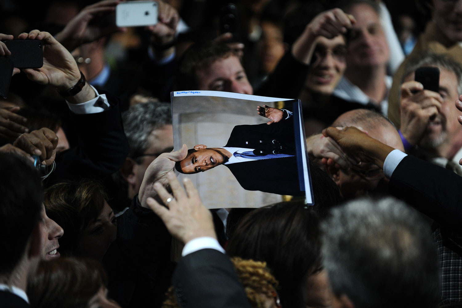 January 11, 2012. A supporter holds a picture of US President Barack Obama during a campaign event at the University of Illinois at Chicago in Chicago, Illinois.