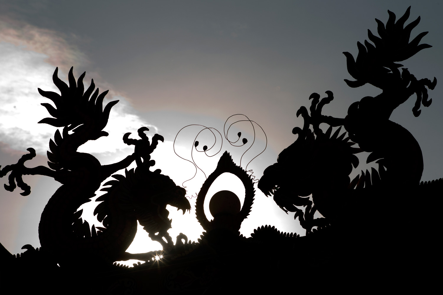January 23, 2012. Dragons statuettes are silhouetted during sunrise at a temple in Kuala Lumpur. The Lunar New Year marks the start of the Year of the Dragon.