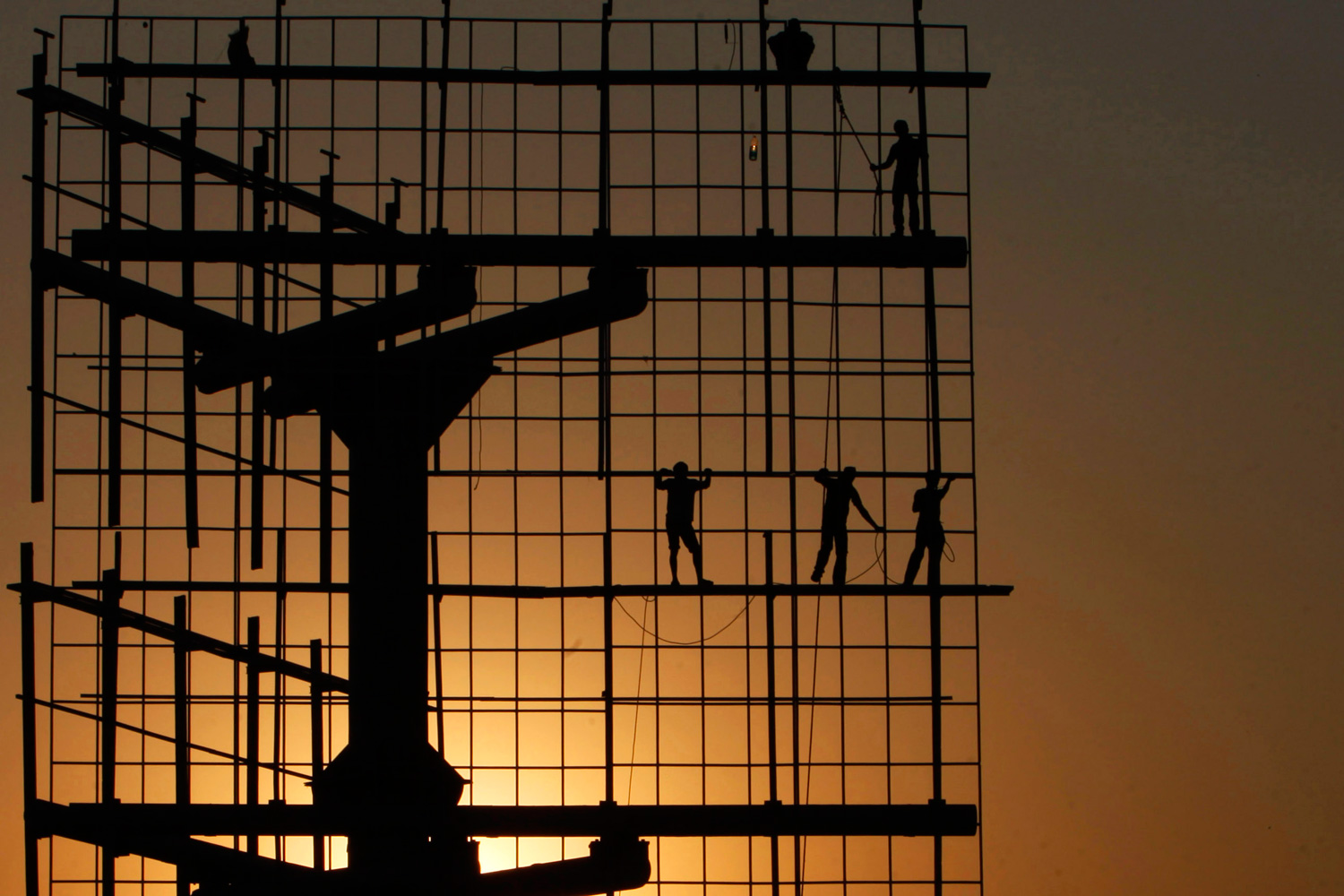 January 17, 2012. Indian workers prepare to erect a hoarding as the sun sets in Hyderabad, India.