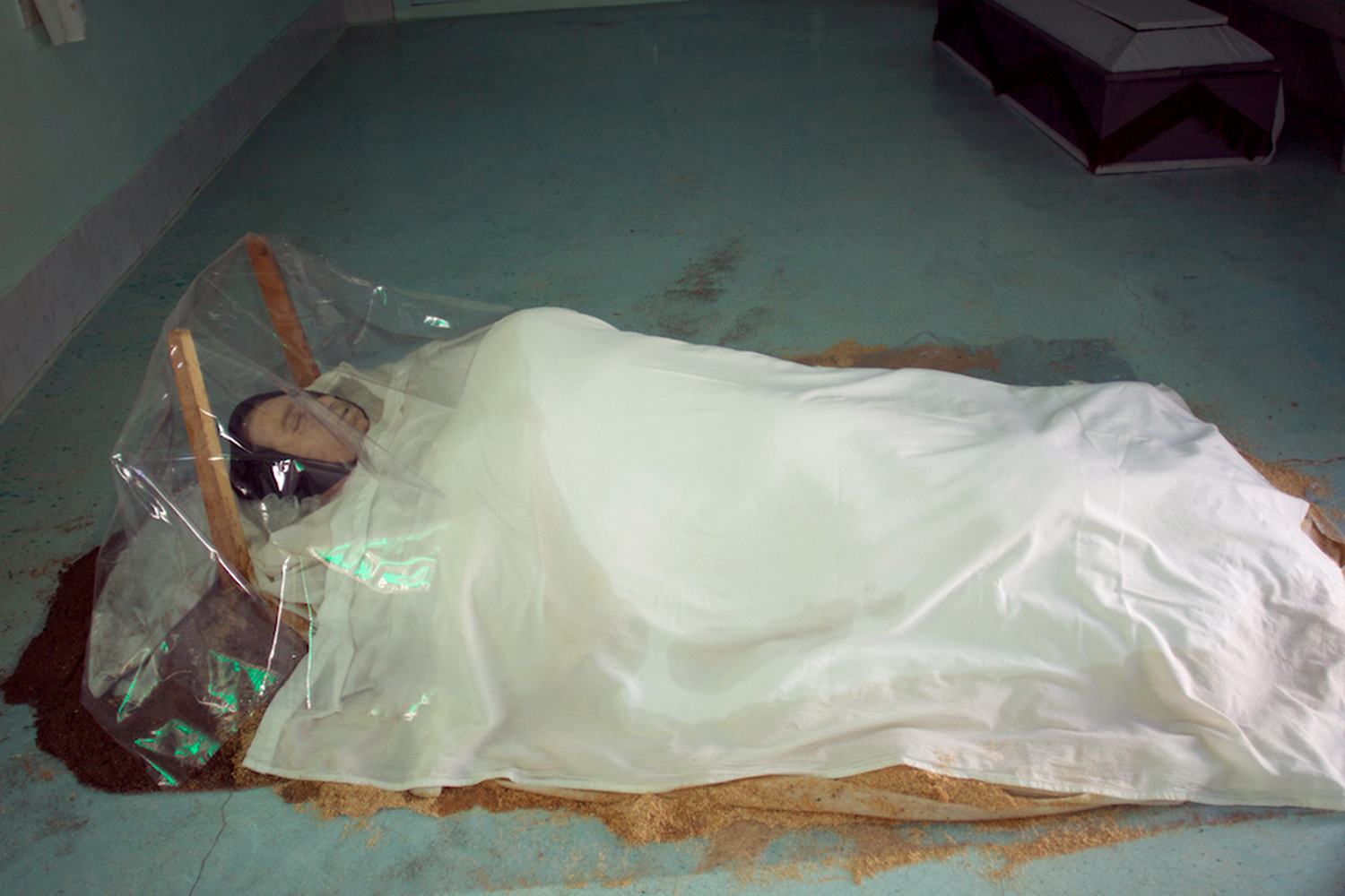 Dead woman laying under dirt, ice and sawdust within the place she died from heart disease. Her community pays her mourning by visiting the place for the next three days, Nuevo Ideal, Durango, Mexico, 2010