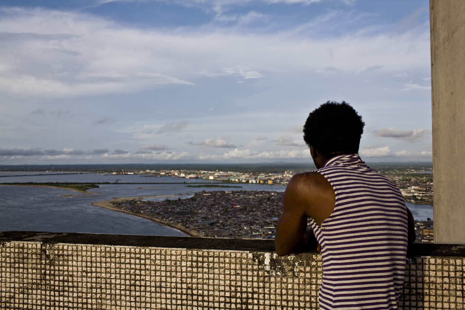 A man looks out over downtown Monrovia from the Ducor, once a four-star hotel.