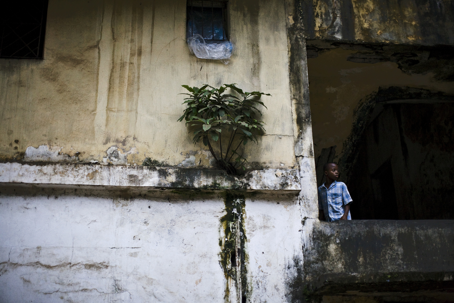 A young boy looks out of a decaying building in Monrovia. Though many buildings have been repaired since the war, much is still in disrepair.