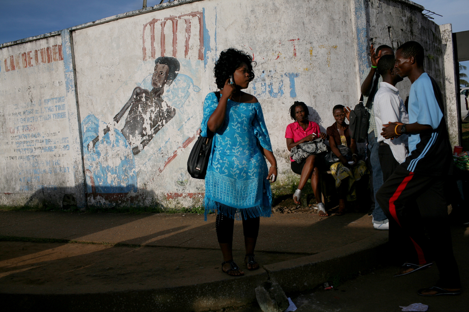 A woman waits for transportation outside of the Health Ministry in Monrovia.