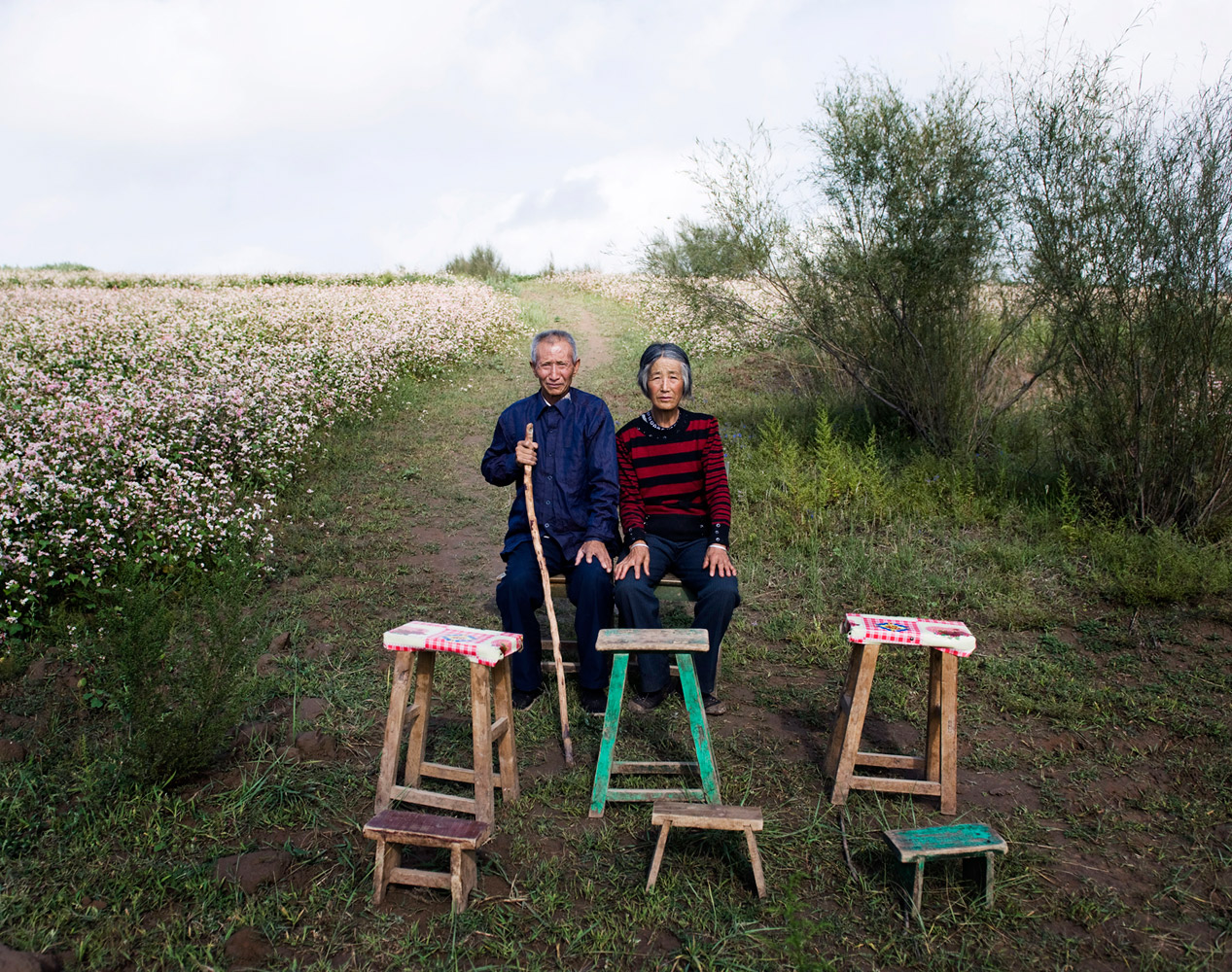 Scholarship winner Liu JieTian Yunxiu (left) and his wife Liu Dezhen sit beside six empty seats in an undeveloped village in Shan'xi province of western China, August 24, 2011. There are six young people from Tian Yunxiu's family who left their village to find jobs in cities.