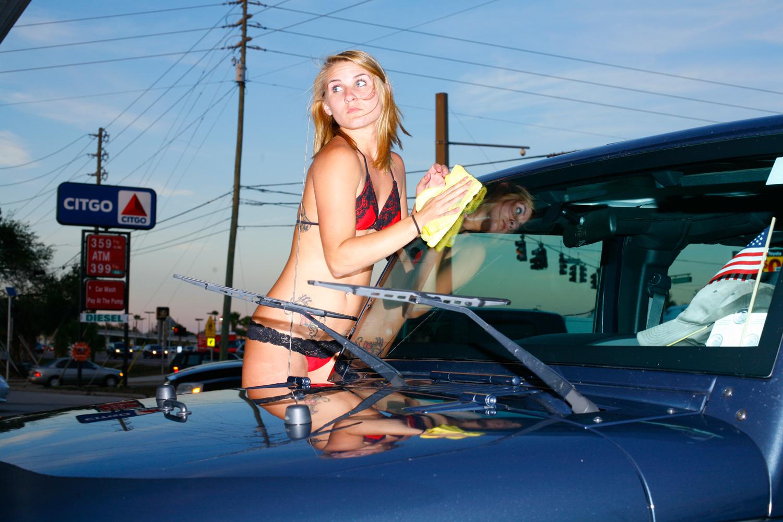 An employee washes a car at the BayWash Bikini Car Wash in Winter Park, Fla., January 28, 2012.