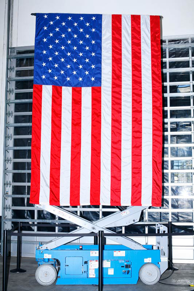 A flag decorates Romney's campaign event at Ring Power Lift Trucks in Jacksonville, Fla., January 30, 2012.
