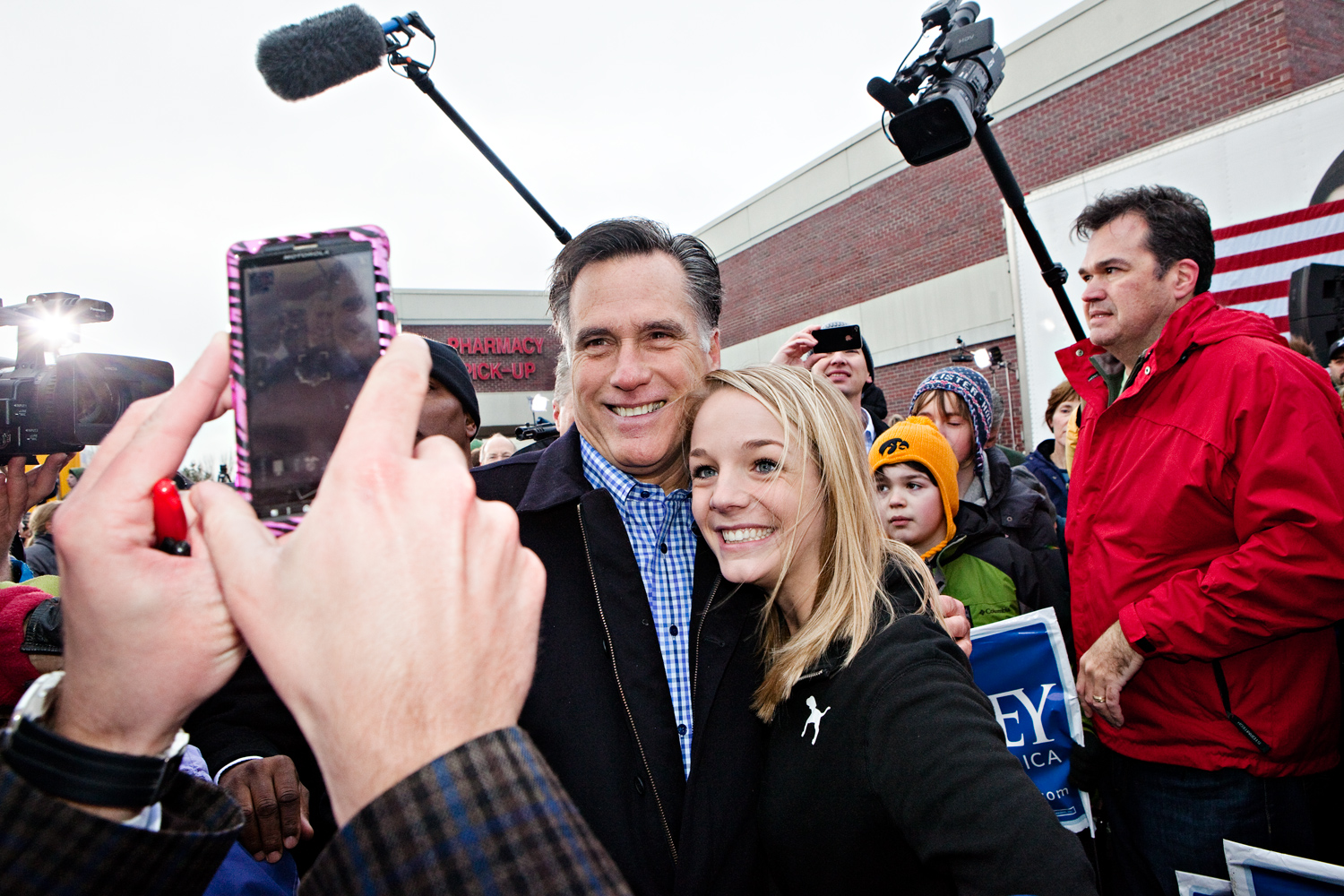 Mitt Romney poses for photos with a young supporter at a campaign event at the Hy-Vee parking lot in West Des Moines, Iowa on December 30, 2011.