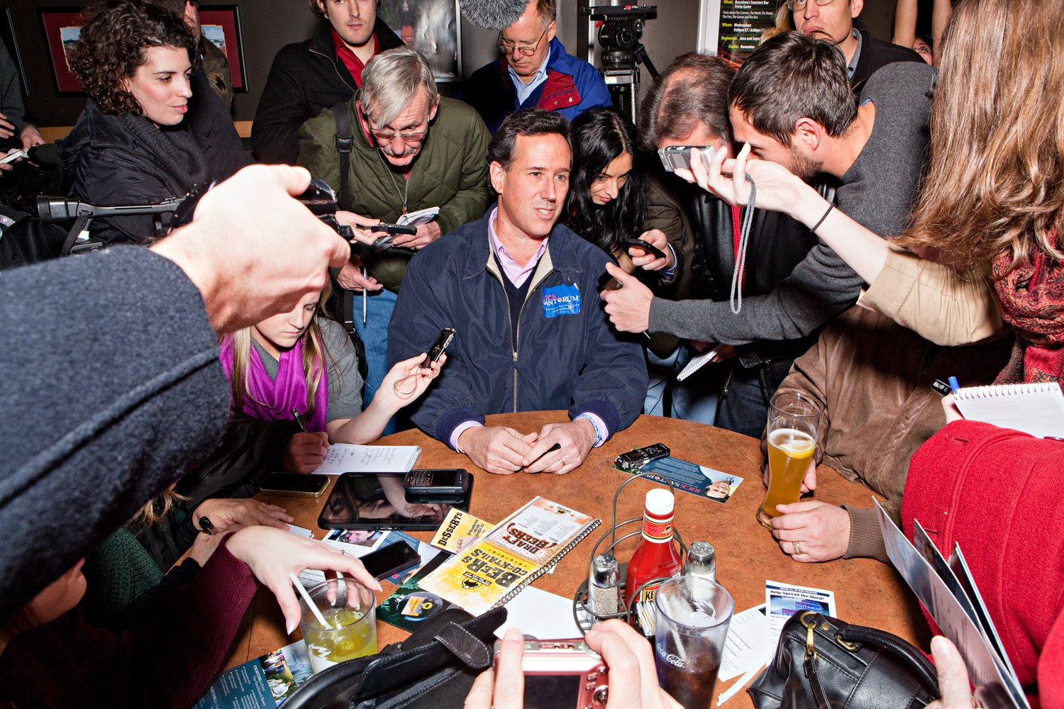 The press questions Rick Santorum as he campaigns at Buffalo Wild Wings in Ames, Iowa on December 30, 2011.