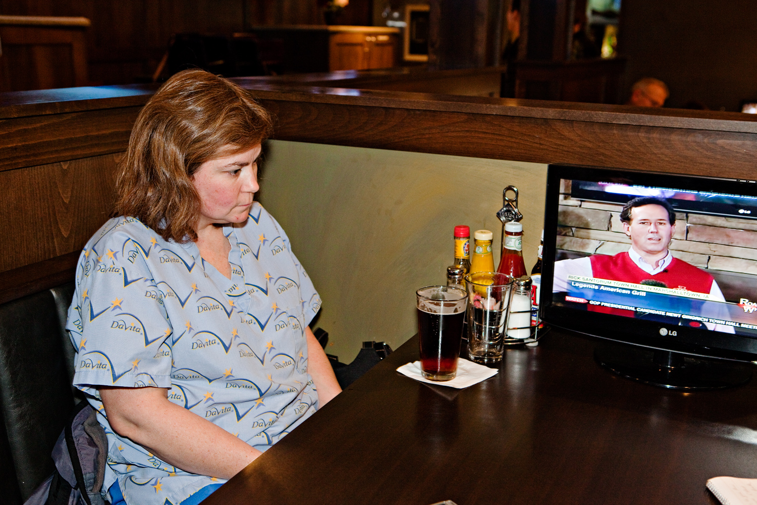 A woman watches Rick Santorum on a closed curcuit TV during a campaign event at Legends American Grill in Marshalltown, Iowa on December 30, 2011.